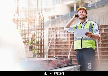 Ingenieur mit digital-Tablette reden über Handy auf Baustelle - Stockfoto
