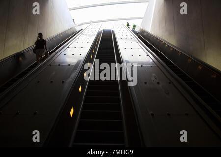 Eine Rolltreppe mit Passagieren durchläuft Ovalrohr des Lichts, die Washington D.C. Metrorail-Pendelzüge - Stockfoto