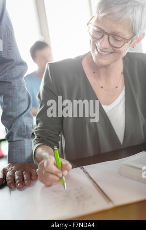 Ältere Frau, die Überprüfung der Hausaufgaben in Erwachsenenbildung Klassenzimmer - Stockfoto