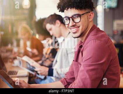 Porträt, Lächeln Mann mit lockiges schwarzes Haar mit digital-Tablette im café - Stockfoto