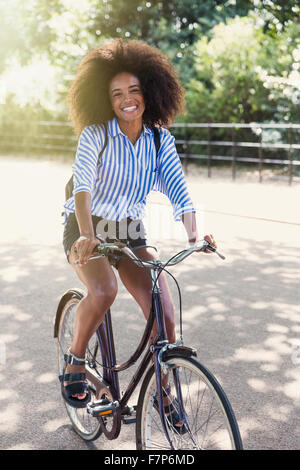 Porträt lächelnde Frau mit Afro Reiten Fahrrad im park - Stockfoto