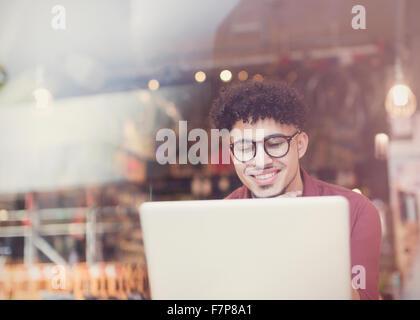 Lächelnder Mann mit lockiges schwarzes Haar mit Laptop im Café Fenster - Stockfoto