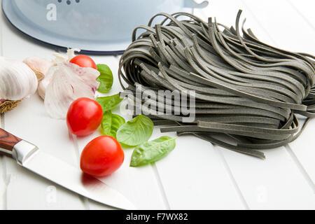 Nudeln, Knoblauch, Tomaten und Basilikum Blätter auf weißen Tisch - Stockfoto