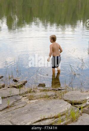 Rückansicht eines jungen zu Fuß im Teichwasser - Stockfoto
