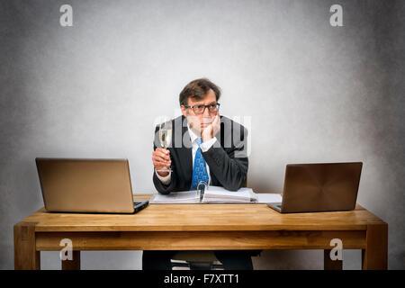 Bild der frustrierte einsame Geschäftsmann mit Sektglas im Büro - Stockfoto