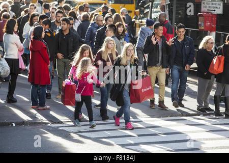 Mutter und Töchter shopping für Urlaub präsentiert am schwarzen Freitag zu Fuß in der 5th Avenue in New York City. - Stockfoto