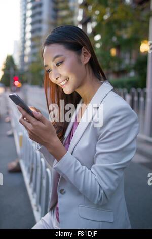 Junge Frau wartet auf Taxi mit Smartphone - Stockfoto
