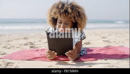 Frau benutzt eine Tablette am Strand - Stockfoto