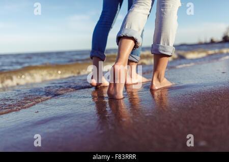 Füße des Paares. Frau und Mann in den Wellen des Meeres auf dem sunset - Stockfoto