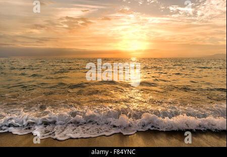 Strand Sonnenuntergang ist ein golden sunset Himmel mit einer Welle ans Ufer Rollen, als den Sonnenuntergang über - Stockfoto