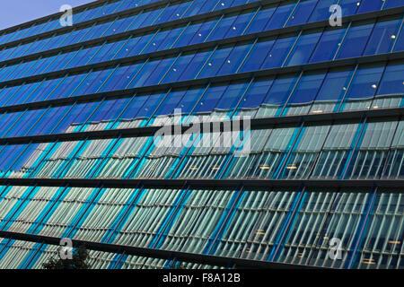 Eine Seitenansicht eines Bürogebäudes mit schattigen blauen Fenstern und die Reflexion des gegenüberliegenden Gebäudes - Stockfoto