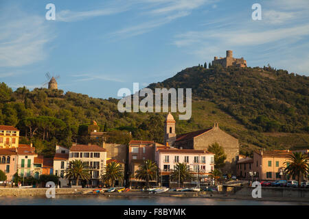 Schönen Abendlicht auf die Stadt Collioure, Südfrankreich, mit der historischen Windmühle & Fort Saint-Elme im Hintergrund. - Stockfoto