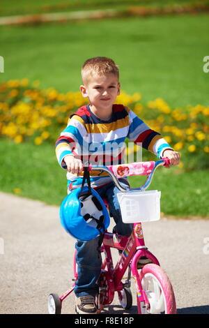glücklicher kleine Junge haben Spaß im Park und seinem ersten Fahrrad fahren zu lernen - Stockfoto