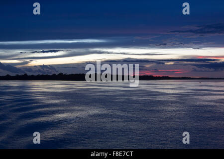 Lila blau Sonnenuntergang auf dem Fluss Amazonas mit den Silhouetten der Bäume. Bundesstaat Amazonas, Brasilien - Stockfoto