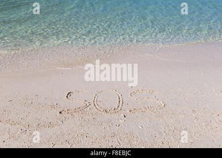 SOS ausgeschrieben im nassen Sand an einem tropischen Strand in Thailand - Stockfoto