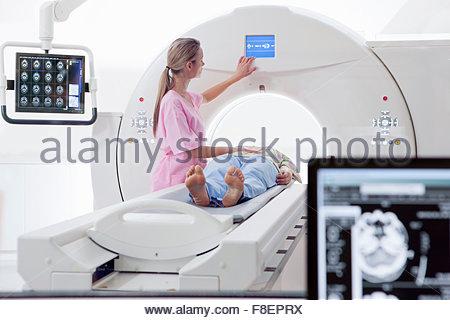 Krankenschwester Techniker und Patienten bei CT-Scanner im Krankenhaus mit digitalen Gehirn-Scan im Vordergrund - Stockfoto