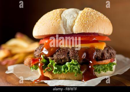 Einen köstlichen chaotisch hausgemachten Speck Cheeseburger mit Barbecue-Sauce, Salat, Tomaten und Zwiebeln.