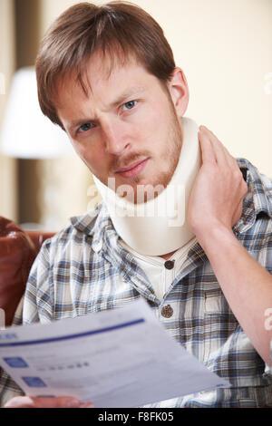 Mann trägt chirurgische Kragen lesen schreiben - Stockfoto