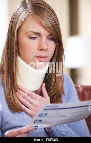 Junge Frau trägt Neck Brace lesen schreiben - Stockfoto