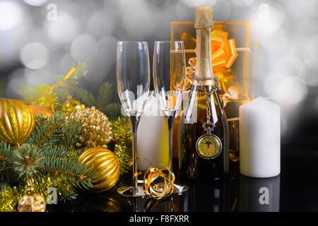 Funkelnde festlichen Stillleben - antike Taschenuhr hängen vom Hals der Flasche Champagner, umgeben von eleganten - Stockfoto