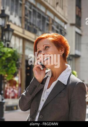 Kaukasische Geschäftsfrau, reden über Handy in Stadt - Stockfoto