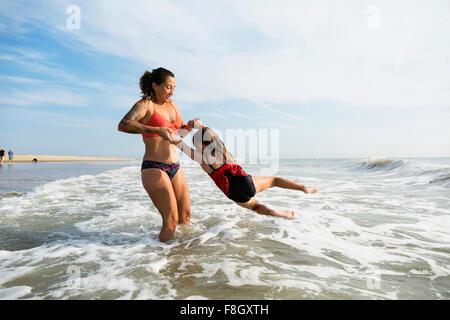 Mutter und Tochter spielen in Wellen am Strand