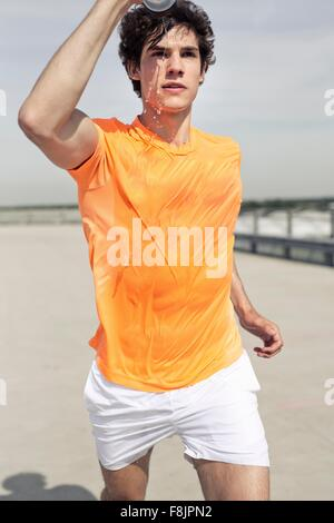 Junge männliche Läufer gießt Wasser auf seinem Gesicht während Stadt laufen - Stockfoto