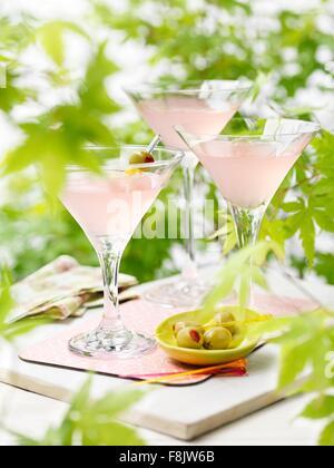 Drei Gläser von rosa Grapefruit und Martini-Cocktails mit grünen Oliven - Stockfoto