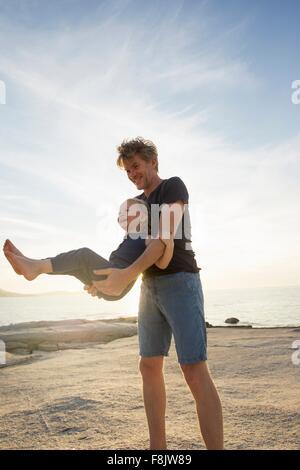 Reifer Mann schwingt seine Kleinkind Tochter am Strand, Calvi, Korsika, Frankreich - Stockfoto