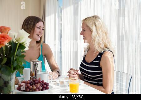 Frauen sitzen am Esstisch genießen Sie ein kontinentales Frühstück zusammen, von Angesicht zu Angesicht lächelnd - Stockfoto