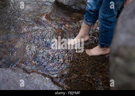 Beine und nackte Füße der weiblichen Kleinkind baumelnd über rockpool - Stockfoto