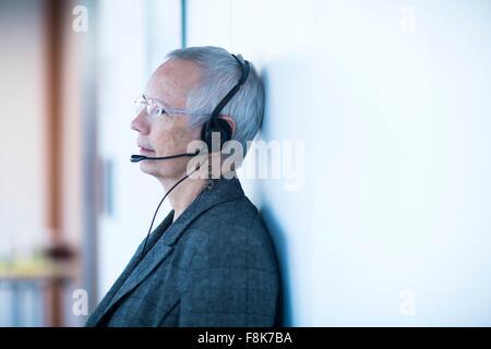 Seitenansicht des Reife Frau tragen Telefon Kopfhörer wegsehen Wand gelehnt - Stockfoto