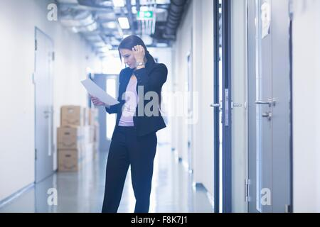 Junge Frau im Büro Korridor blickte auf Papierkram Kopf kratzen - Stockfoto