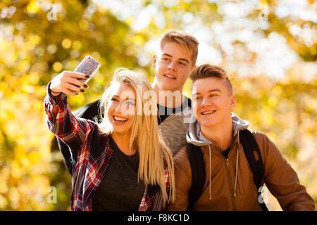 Junge Frau, die die Selfie mit zwei Teenager-Brüder im herbstlichen Wald - Stockfoto