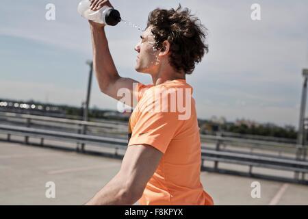 Junge männliche Läufer gießt Wasser auf seinem Gesicht, während des Laufens in Stadt - Stockfoto