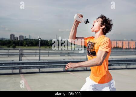 Junge männliche Läufer Trinkwasser während Stadt laufen - Stockfoto