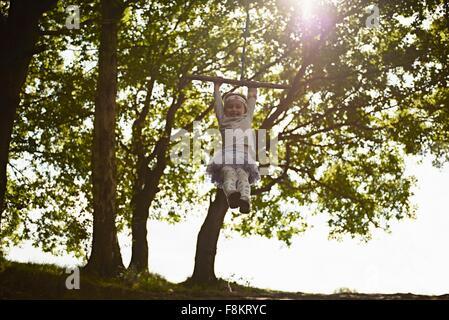 Junges Mädchen auf Baum schwingen schwingen - Stockfoto