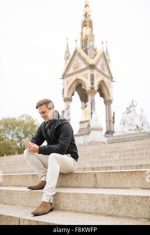 Junger Mann sitzt auf Schritte lesen Smartphone Texte, Albert Memorial, London, England, UK - Stockfoto