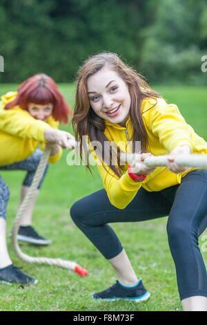 Junge Frauen spielen Tauziehen auf Feld - Stockfoto