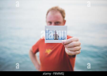 Mann hält Foto von sich selbst See - Stockfoto