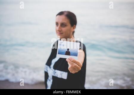 Frau hält Foto von sich selbst am Strand - Stockfoto