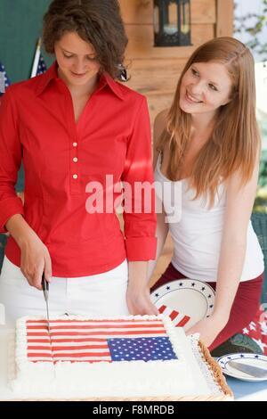Frau schneiden Kuchen am 4. Juli (USA) - Stockfoto
