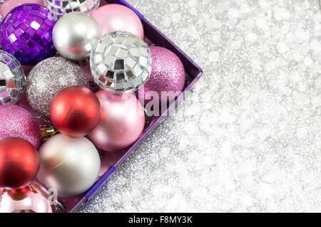 Bunte Weihnachtskugeln in einer Schüssel vor glänzenden silbernen Hintergrund - Stockfoto