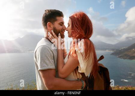 Porträt des jungen Mann und Frau zu einen romantischen Kuss zu teilen. Liebevolle junge Paar genießen ihre Liebe - Stockfoto