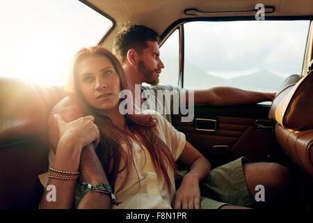 Schuss von junge Frau mit ihrem Freund sitzt auf dem Rücksitz eines Autos auf Reise gehen. Paar in der Rückbank - Stockfoto