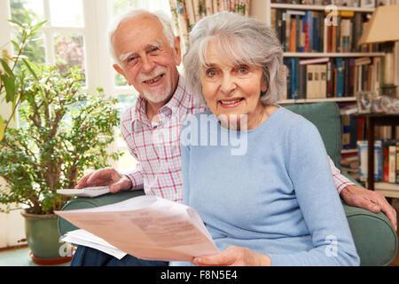 Gerne älteres Paar, die Überprüfung der Finanzen zu Hause - Stockfoto