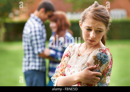 Einsame eifersüchtig Teenager-Mädchen mit romantisch zu zweit im Hintergrund - Stockfoto