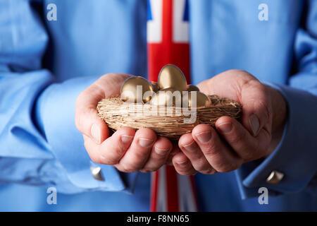 Geschäftsmann mit Union Jack Krawatte Nest goldene Eier halten - Stockfoto