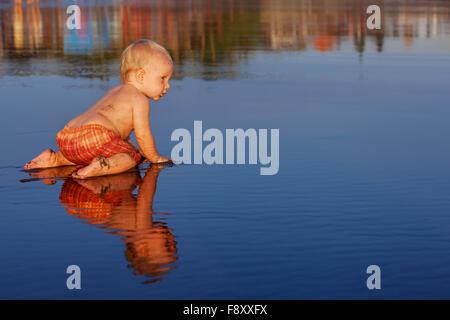 Auf Sonnenuntergang Strand lustige Baby Boy kriechen auf glatte schwarze nassen Sand ins Meer zum Schwimmen in Wellen - Stockfoto