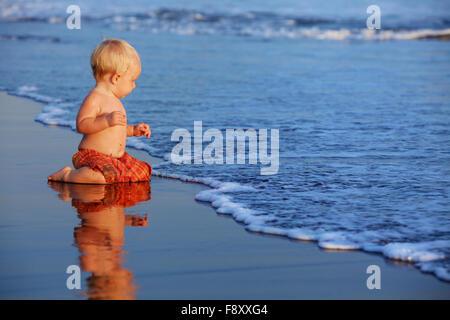 Am Sonnenuntergang Strand lustige Baby sitzen auf schwarzen nassen Sand und Meer Surfen zum Schwimmen in Wellen - Stockfoto
